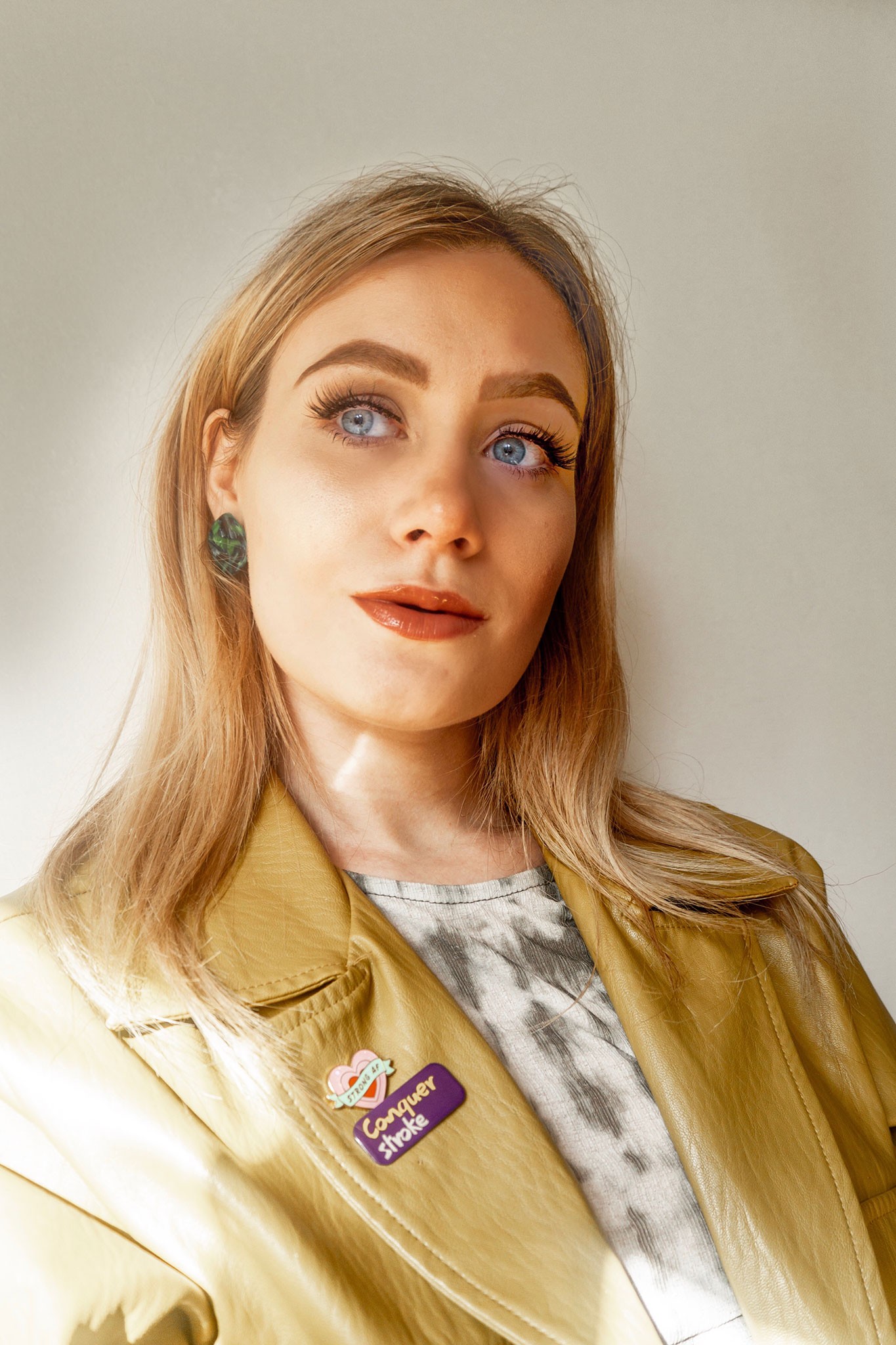 girl looking on in thought wearing conquer stroke and strong af pin badge